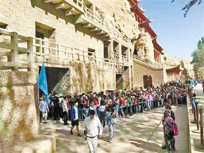 """参观敦煌莫高窟的游客排起了""""长龙""""。记者谭安丽摄"""